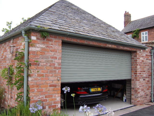Green remote controlled roller garage door title=